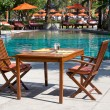 Stock Photo: Table and chairs next to the pool, Thailand