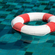 Life ring floating on top of sunny blue water — Stock Photo
