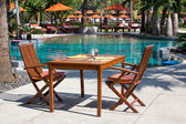 Table and chairs next to the pool, Thailand — Stock Photo