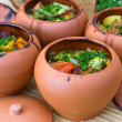 Foto Stock: Meat baked with vegetables in rustic clay pot