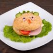 Fun food for kids - hamburger looks like a funny muzzle — Stock Photo #29890221