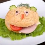 Fun food for kids - hamburger looks like a funny muzzle — Stock Photo #30244697