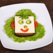 Fun food for kids - face on bread, made from cheese, lettuce, tomato, cucumber and pepper. — Stock Photo #30244793
