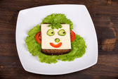 Fun food for kids - face on bread, made from cheese, lettuce, tomato, cucumber and pepper. — Stockfoto