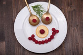 Fun food for kids - face on a plate of raspberries — Stock Photo