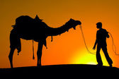 Silhouette of a man and camel at sunset in the desert, Jaisalmer - India — Stock Photo