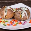 Baked potato with vegetables and sour cream — Stock Photo