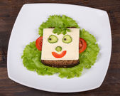 Fun food for kids - face on bread, made from cheese, lettuce, tomato, cucumber and pepper. — Stock Photo