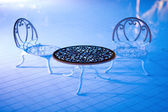 Two chairs and a table stand in the pool — Stock Photo