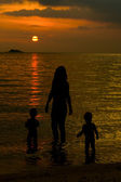 Mother and her kids silhouettes on beach at sunset — Stock Photo