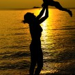 Stock Photo: Mother and her kid silhouettes on beach at sunset