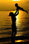 Mother and her kid silhouettes on beach at sunset — Stock Photo