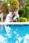 Bride and groom jumping in swimming pool — Stock Photo