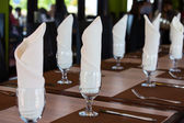 Glasses with a napkin on the table in a restaurant — Stok fotoğraf