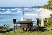Table and chairs next to the sea in island Panglao, Philippines — Stock Photo