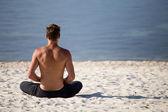 Sitting man doing yoga on shore of ocean — Stock Photo