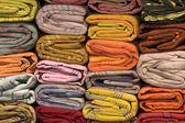 Heap of cloth fabrics at a local market in India. Close up . — Stock Photo