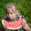 Adorable blonde girl eats a watermelon outdoors — Stock Photo #47434397