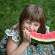 Adorable blonde girl eats a watermelon outdoors — Stock Photo