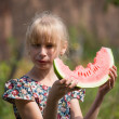 Adorable blonde girl eats a watermelon outdoors — Stock Photo #47434405