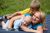 Happy mother and two sons in the park — Stock Photo