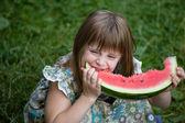 Adorable blonde girl eats a watermelon outdoors — Stock Photo