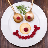Face on a white plate of raspberries — Stockfoto