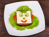 Face on bread, made from cheese, lettuce, tomato, cucumber and pepper — Stock Photo