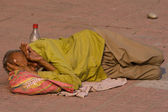 Homeless man sleeps on the sidewalk near the River Ganges in Haridwar, India. — Stock Photo