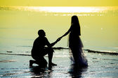 Newlyweds on the beach during sunset — Stock Photo