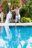 Newlyweds jumping in swimming pool — Stock Photo