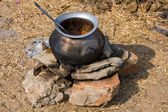 Metal  pot with food on fire, India — Stock Photo