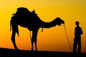 Silhouet van een man en de kameel bij zonsondergang in de woestijn, jaisalmer - india — Stockfoto