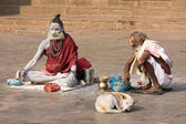 Sadhu sits on the ghat along the Ganges river in Varanasi, India. — Stock Photo