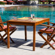 Table and chairs in empty cafe next to the pool — Stock Photo #50523247