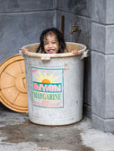 Homeless girl bathes in a plastic bucket, Philippines — Stock Photo