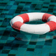 Life ring floating on top of sunny blue water — Stock Photo #51021611