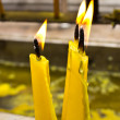 Three burning yellow candles — Stock Photo #42751303