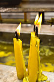 Three burning yellow candles — Stockfoto