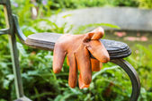 Orange plastic gloves on arm chair in the park — Stock Photo