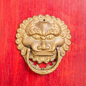 Ancient red doors with gilded studs and lion head door knockers — Stock Photo