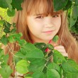 Stock Photo: Little girl hiding behind tree