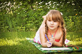 Girl lying on the grass and draws — Stock Photo