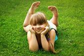 Little girl lying on grass — Stock Photo