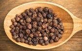 Black pepper grains in spoon — Stock Photo
