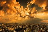 Raios de luz brilhando através da cidade de nuvens escuras — Fotografia Stock