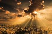 Rays of light shining through dark clouds city — Stok fotoğraf