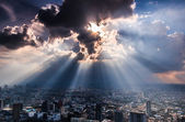 Promienie światła wpadające przez miasto ciemne chmury — Zdjęcie stockowe