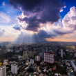 Rays of light shining through dark clouds city — Stock Photo