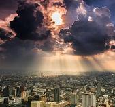 Лучи света, сквозь темные тучи город — Стоковое фото